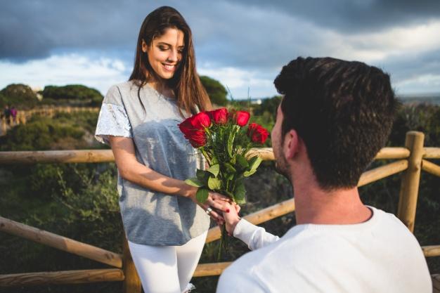 man-kneeling-handing-bouquet-roses-woman_23-2147595899
